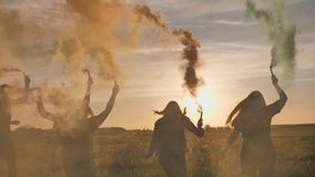 Happy friends waving colorful smoke at sunset. Happy friends waving colorful smoke at sunset stock video footage