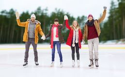 Happy friends waving hands on outdoor skating rink Stock Images