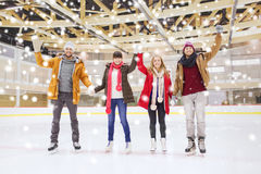 Happy friends waving hands on skating rink Royalty Free Stock Photos