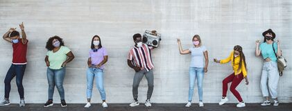 Happy friends wearing face mask listening music with vintage boombox outdoor - Multiracial young people having fun dancing