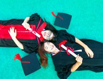 Happy friendship from college graduated. Two girls in black gowns laying down on green background and hold diploma certificate with happy graduated stock photos