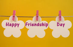 Happy Friendship Day message greeting across white flower tags hanging from pegs on a line. Against a bright fun yellow background, for International Friendship Royalty Free Stock Image