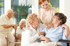 Happy friendship in old age. Tender caregiver standing behind se stock photography