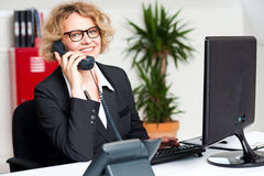 Happy front desk lady attending clients call. Front desk lady attending call and working on computer Royalty Free Stock Photography