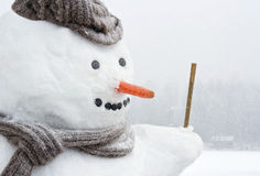 Happy frosty snowman outdoors in snowfall. Closeup of smiling snowman with woolen hat, scarf and carrot nose, outdoors in snowfall royalty free stock photos