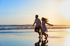 Family - father, mother, baby run on sunset beach. Happy full family - father, mother, baby son have fun together, child run with splashes by water pool along Royalty Free Stock Photos