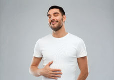 Happy full man touching tummy over gray background Stock Images