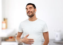 Happy full man touching tummy over kitchen Stock Image