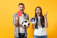 Happy fun expessive crazy couple, woman man football fans screaming, cheer up support team with soccer ball, megaphone. Fun expessive crazy couple, woman man stock photography