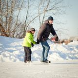 Happy fun father and son learning to skate Stock Image