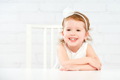 Happy fun funny girl child laughing at  empty white table Royalty Free Stock Photos