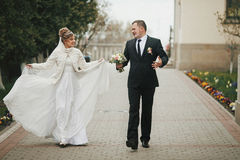 Happy fun newlywed couple walking on alley road in autumn.  Royalty Free Stock Image
