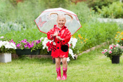 Happy fun pretty little girl in red raincoat with umbrella walking in park summer. Ladybug costume, portrait, rain, outdoor Stock Photography