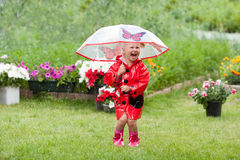Happy fun pretty little girl in red raincoat with umbrella walking in park summer. Ladybug costume, portrait, rain, outdoor Stock Images