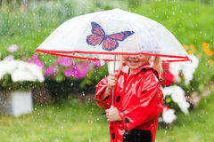 Happy fun pretty little girl in red raincoat with umbrella walking in park summer. Ladybug costume, portrait, rain, outdoor Royalty Free Stock Image