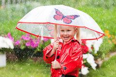 Happy fun pretty little girl in red raincoat with umbrella walking in park summer. Ladybug costume, portrait, rain, outdoor Royalty Free Stock Photography