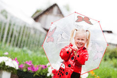 Happy fun pretty little girl in red raincoat with umbrella walking in park summer. Ladybug costume, portrait, rain, outdoor Royalty Free Stock Photos