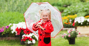 Happy fun pretty little girl in red raincoat with umbrella walking in park summer. Ladybug costume, portrait, rain, outdoor Royalty Free Stock Photo
