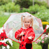 Happy fun pretty little girl in red raincoat with umbrella walking in park summer. Ladybug costume, portrait, rain, outdoor Royalty Free Stock Images