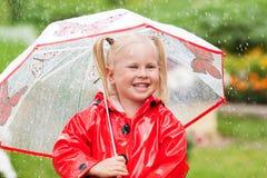 Happy fun pretty little girl in red raincoat with umbrella walking in park summer. Ladybug costume, portrait, rain, outdoor Stock Photo