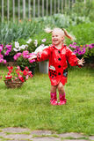 Happy fun pretty little girl in red raincoat with umbrella walking in park summer Royalty Free Stock Photo
