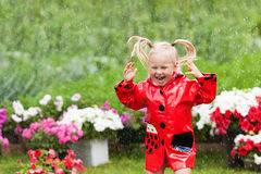 Happy fun pretty little girl in red raincoat with umbrella walking in park summer Royalty Free Stock Image