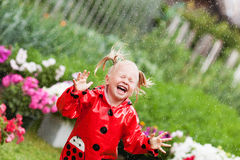Happy fun pretty little girl in red raincoat with umbrella walking in park summer Stock Images