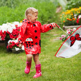 Happy fun pretty little girl in red raincoat with umbrella walking in park summer Stock Photo