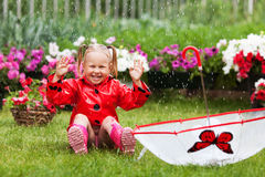 Happy fun pretty little girl in red raincoat with umbrella walking in park summer Royalty Free Stock Images