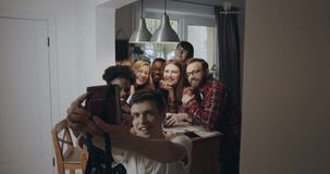 Happy fun young multiethnic friends take an instant selfie group photo sitting together in kitchen at party slow motion. stock video