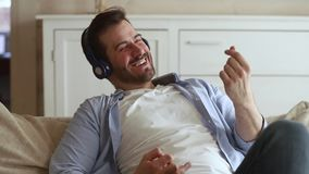 Happy man sitting on couch wearing headphones listening to music. Happy funky young man sitting on couch wearing wireless headphones listening to music, smiling stock video