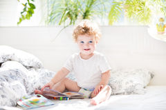 Happy funny baby reading book in her parents bed Royalty Free Stock Images