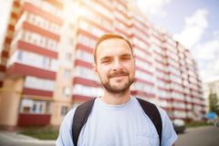 Happy funny bearded student man in blue t-shirt with backpack standing in front of the new building flat house dormitory. Hipster posing for photo smiling stock photos