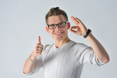 Happy funny boyfriend show sight thumbs up and ok. Portrait of a happy  smiling happy casual man showing gesture ok and thumbs up with fingers standing on gray Stock Image