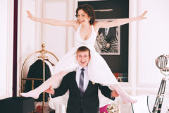 Happy funny bride sitting on groom shoulders Stock Images