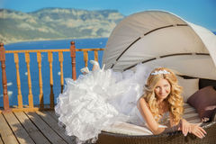 Happy funny bride in white wedding dress lying on sofa over the Stock Photo