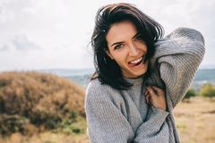 Happy and funny brunette woman smiling and stick out tongue against nature meadow background with windy hair, having fun during. Her vacation in mountain stock photos