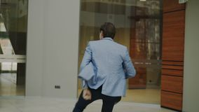 Happy and funny businessman with briefcase dancing in office lobby while nobody watching him stock footage