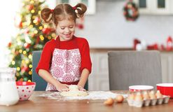 Happy child girl bake christmas cookies. Happy funny child girl bake christmas cookies royalty free stock photos