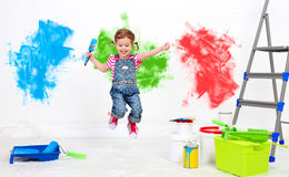 Happy funny child girl doing repairs, jumping and paint wall Stock Photo