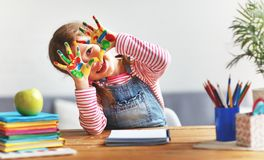 Funny child girl draws laughing shows hands dirty with paint royalty free stock photo