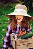 Happy funny child girl in farmer hat and shirt playing and picking autumn vegetable harvest. In sunny garden. Growing organic carrots and pumpkins Stock Images
