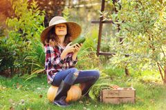 Happy funny child girl in farmer hat and shirt playing and picking autumn vegetable harvest. In sunny garden. Growing organic carrots and pumpkins Stock Image