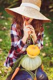 Happy funny child girl in farmer hat and shirt playing and picking autumn vegetable harvest in sunny garden. Growing organic carrots and pumpkins Royalty Free Stock Photos