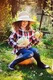 Happy funny child girl in farmer hat and shirt playing and picking autumn vegetable harvest stock images
