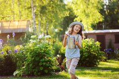 Happy funny child girl in gardener hat playing with watering can. In sunny summer garden Stock Images