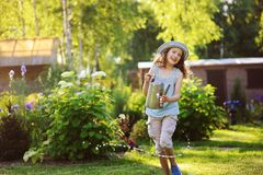 Happy funny child girl in gardener hat playing with watering can. In sunny summer garden Stock Photography