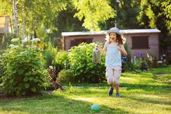 Happy funny child girl in gardener hat playing with watering can. In sunny summer garden Royalty Free Stock Image