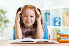 Happy funny child girl in glasses reading a book Royalty Free Stock Photos