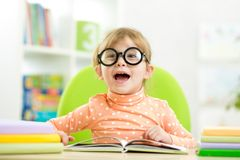 Happy funny child girl in glasses reading a book Stock Photography